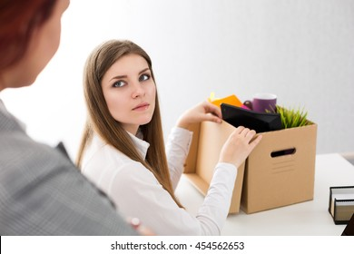 Boss dismissing an employee. Dejected fired office worker looking at her boss and packs her belongings to carton box. Getting fired concept.