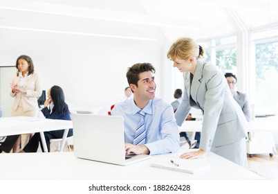 A Boss Guiding her Employee in Front of the Laptop