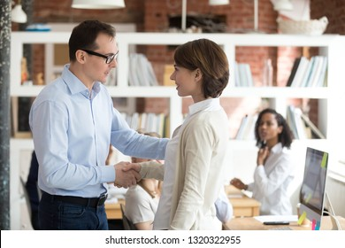 Boss handshaking shy woman standing in shared office, diverse colleagues looking at new employee with curiosity. Promoted worker, hiring human resources or reward and gratitude for great work concept
