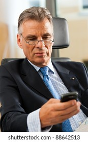 Boss in his office checking mails and reading newspapers