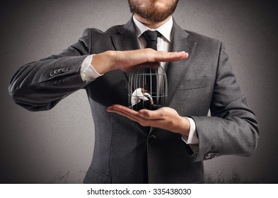 Boss holds in hands a caged man