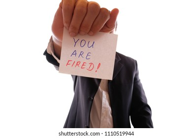 "Boss holds a note to the employee ""You Are Fired!"" in front of the face"