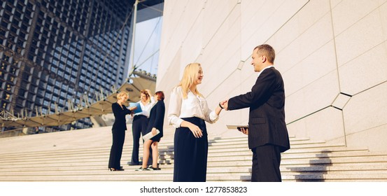 Boss keeping tablet and speaking with blonde secretary on stairs with biz partners in background. Concept of decision making and successful ideas. Business persons talking and waiting for conference.