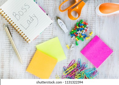 Boss lady work from home desk with office supplies including notebook, scissors, stapler, jump drive, push pins, post it notes, pen, and paper clips