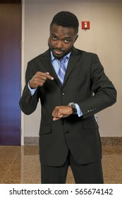 Boss man telling someone they are late by pointing at his watch