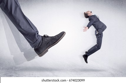Boss mobbing his worker, illustrated by black shoe kicking small businessman who is flying away in the space
