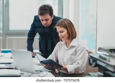 Boss monitoring employee's progress in the office