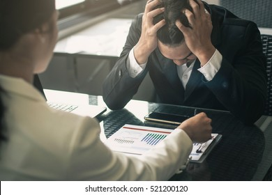 Boss scolding a shameful employee at work in an office. Businessman with sad expression working with boss.Worried businessman working trying to solve troubles.