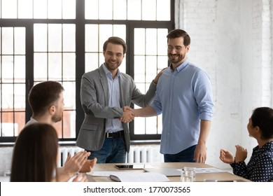 Boss shake hands introduces new employee to members during briefing in board room, staff clap hands encourage newcomer welcoming express regard. Praise and appreciation, best worker of month concept