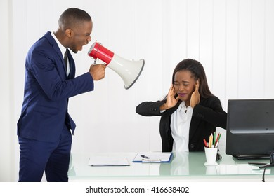 Boss Shouting At Young Businesswoman Through Loudspeaker In Office