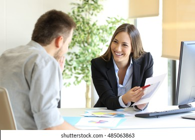 Boss showing a good job congratulating an employee at office