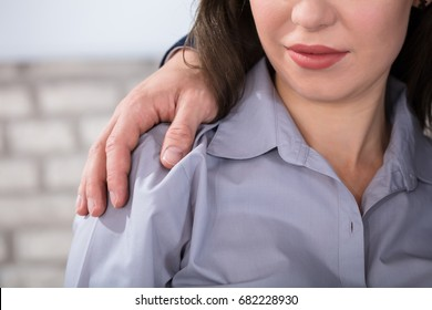 A Boss Touching The Shoulder Of Female Colleague In Workplace At Office