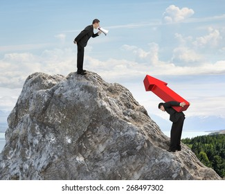 Boss using megaphone commanding employee carrying big 3D red arrow sign on top of mountain peak with sky clouds background