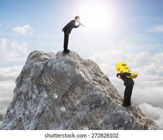 Boss using megaphone commanding employee carrying big 3D euro symbol sign on top of mountain peak with sky clouds sunlight background