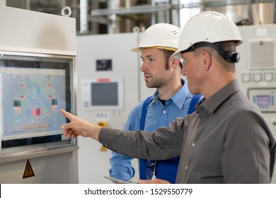 boss with worker in the background in his factory