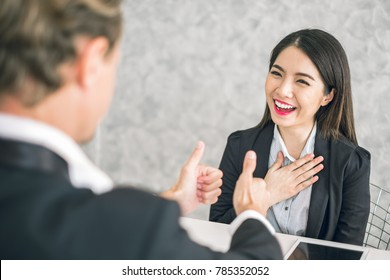 Boss/Business man employer admires young Asian business woman/staff/employee by thumb up and hands clap with smiling face for her success and good/best in work and recognition/appreciate.
