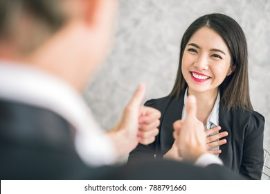 Boss/Business man employer admires young Asian business woman/staff/employee by thumb up and clap with smiling face for her success and good/best in work and recognition/appreciate.