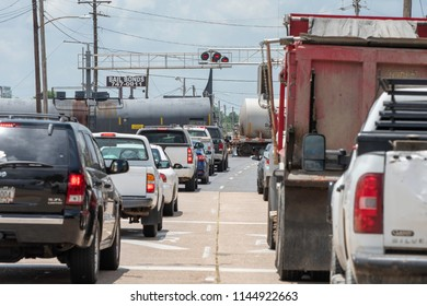 BOSSIER CITY, LA., U.S.A. - JUNE 12, 2018: Evening rush-hour traffic backs up as a freight train pauses at a crossing at a major thoroughfare.