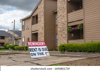 """BOSSIER CITY LA., U.S.A. - March 30, 2020: Despite the covid 19 pandemic shutdown, a sign in the parking lot of an apartment complex reminds renters that """"Rent is due on the 1st."""""""