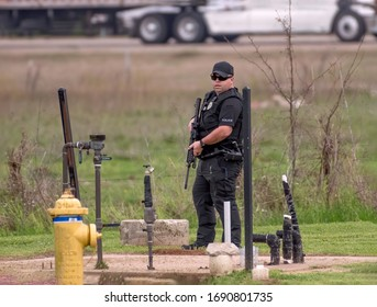 BOSSIER CITY, LA., U.S.A. - MARCH 18, 2020: A Bossier City Police officer in a field adjacent to U.S. Interstate 20, after shots were fired during a fight in a nearby mobile home park.