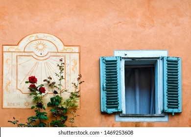 "Bossolasco, Cuneo / Italy - June 30 2019: Close-up of an old window with blue shutters, a blooming red rose climbing on the orange wall and a sundial with the Latin motto ""Life vanishes like a shadow"""