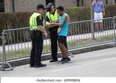 BOSTON - APRIL 17 : Guillermo Briseno of Tlalnepantla Mexico stops to get help from local police on Heartbreak Hill in the Boston Marathon on April 17, 2017 [public race]