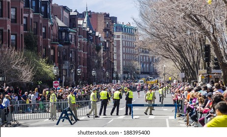 BOSTON - APRIL 21, 2014: Runners in the Boston Marathon approach the finish line surrounded by a clear police presence, a little over a year after the tragic bombings.