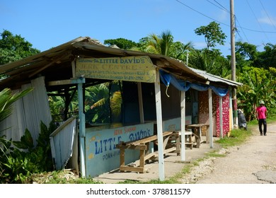 BOSTON BAY, JAMAICA - DECEMBER 30, 2013: Unidentified Jamaican man walking by Little David's Jerk Centre, which is one of the many world famous Jamaican jerk cooking huts in Boston Jerk Center.
