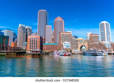 Boston cityscape reflected in water, skyscrapers and office buildings in downtown, view from Boston harbor, Massachusetts, USA