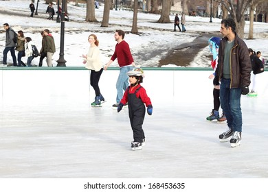 BOSTON - DEC 21: Ice-skating kids with white Christmas in Frog Pond at Boston Common on December 21, 2013 in Boston, Massachusetts