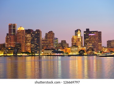 Boston downtown at dusk with urban buildings illuminated at dusk after sunset.