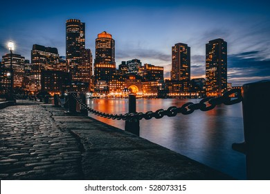 Boston downtown skyline with skyscrapers over water at twilight