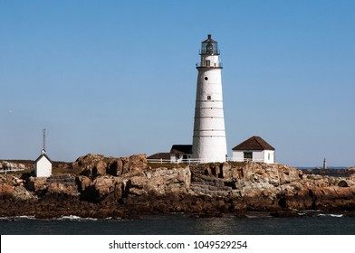 Boston Harbor lighthouse on rocky Little Brewster Island in Autumn. It is the nation'??s oldest lighthouse and favorite destination for tourists.