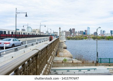 BOSTON, MA - MAY 23, 2019: Transportation background with the Boston Skyline in the background showing cars, MBTA trains, people, and the Charles River.