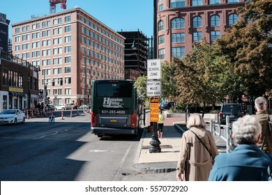 BOSTON, MA, UNITED STATES - CIRCA OCTOBER 2016: Group of adult tourists walking with there guide to a waiting chartered bus in Boston, MA.