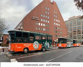 Boston, MA / USA - Jan 2020: Hop on/hop off old town trolleys parked near Marriott Long Wharf Hotel