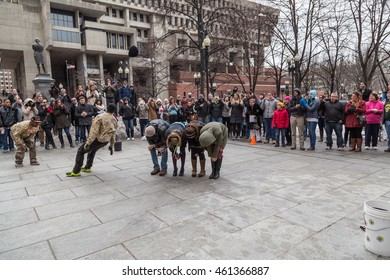 Boston, MA, USA - March 1, 2014: People in winter clothes are watching the Street show at Freedom Trail near the Boston City Hall.