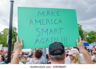 """Boston, MA, USA-June 3, 2017. Protesters at the Anti-Trump March for Truth hold signs at the Boston State House. Prominent sign is 'Make American Smart Again."""""""