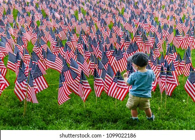 Boston, MA, USA-May 26, 2018. Small boy looks at field of hundreds of US flags planted in Boston Common to commemorate fallen soldiers on Memorial Day.