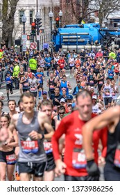 BOSTON, MASSACHUSETTS - APRIL 15, 2019: A crowded field of runners on the last turn towards the finish at mile 26 of the 2019 Boston Marathon.