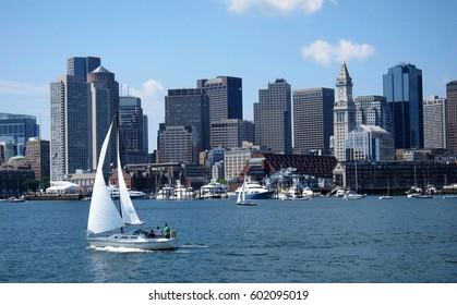 Boston, Massachusetts - July 18 2010. Sail boat crossing Boston harbor with skyline in background