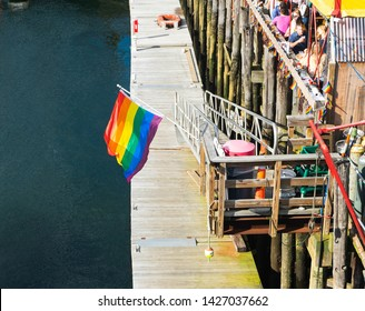BOSTON, MASSACHUSETTS - JUNE 2, 2019: LGBTQ+ Pride flag waving in the wind over the Boston Seaport to celebrate lgbt rights