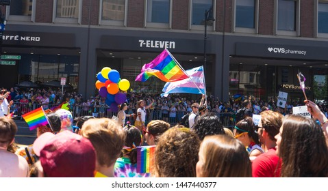 BOSTON, MASSACHUSETTS - JUNE 8, 2019: Crowds of people watching the end of the Boston Pride Parade 2019 with gay pride flags and transgender pride flags in focus