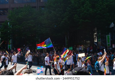 BOSTON, MASSACHUSETTS - JUNE 8, 2019: People marching with an American/Gay Pride Flag at the Boston Pride Parade 2019