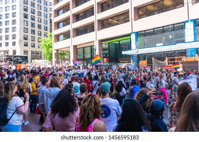 BOSTON, MASSACHUSETTS - JUNE 8, 2019: Crowds of people watching the Boston Pride Parade 2019 with gay pride flags, bisexual flags, and transgender flags in view