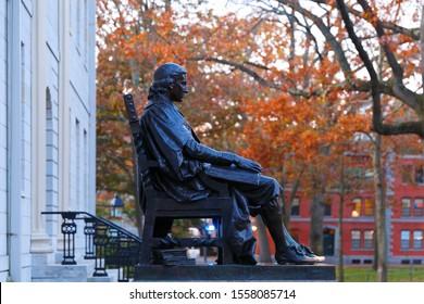 Boston Massachusetts - November 10, 2019: The Statue of John Harvard on campus of Harvard University at sunrise. Harvard University is a private Ivy League research university in Cambridge, MA.