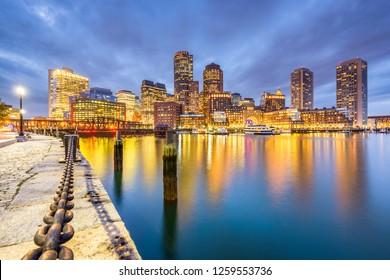 Boston, Massachusetts, USA downtown city skyline from the harbor at dusk.