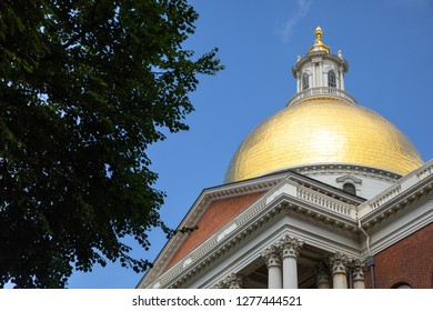 Boston, Massachusetts / USA - July 24 2018: Side close up on the Sacred Cod golden dome atop the Massachusetts State House, framed by tree branches