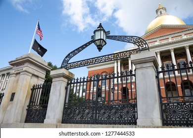 Boston, Massachusetts / USA - July 24 2018: Entrance gates to the Massachusetts State House, with golden Sacred Cod dome in the background