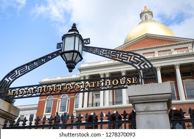 Boston, Massachusetts / USA - July 24 2018: Wrought iron sign and gates at the entrance to the Massachusetts State House, with golden Sacred Cod dome in the background